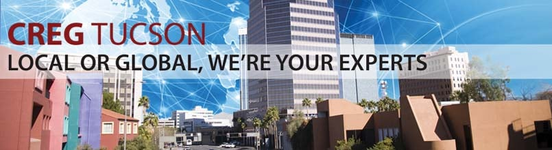 """Local to global, we're your experts"" is a tagline over a photo of downtown Tucson."